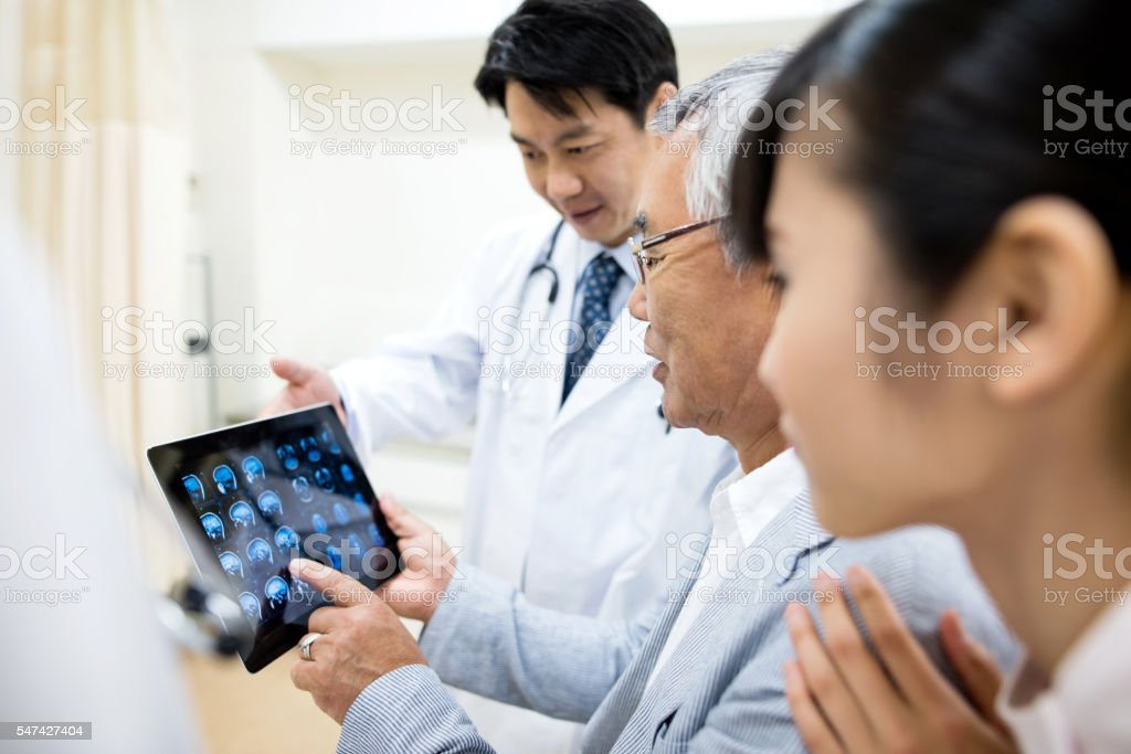Senior patient and doctor looking at medical results stock photo