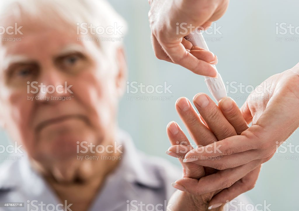 Senior patient doing blood sugar test. stock photo