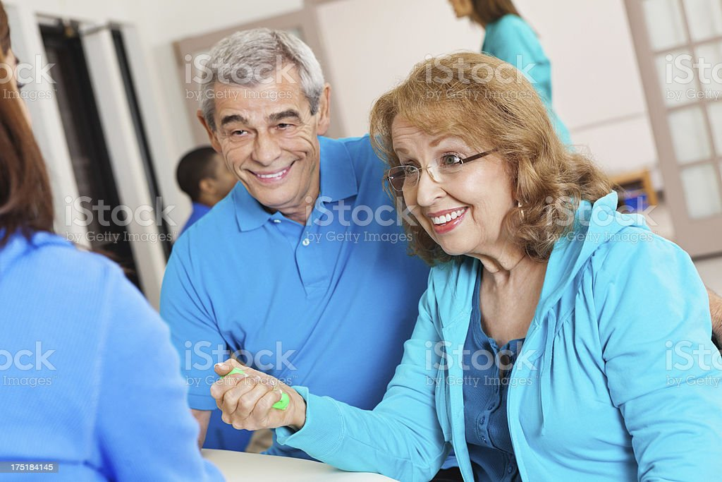 Senior patient doing hand strengthening exercise with physical therapist royalty-free stock photo