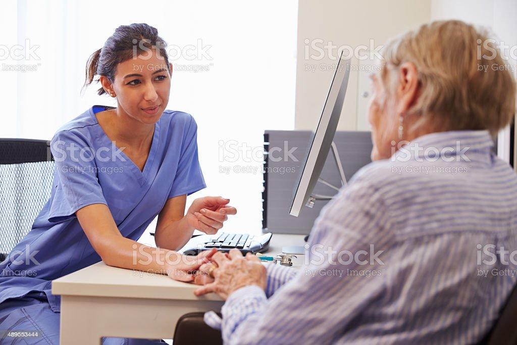 Senior Patient Having Consultation With Nurse In Office stock photo