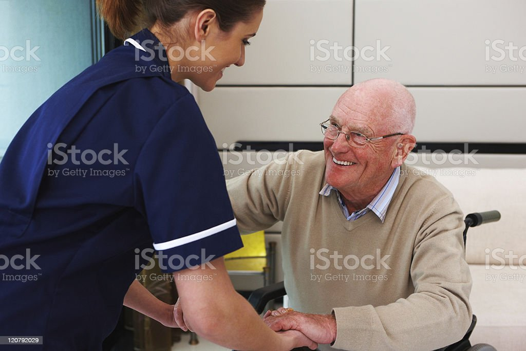 Senior Patient Helped From His Wheelchair by a Nurse royalty-free stock photo
