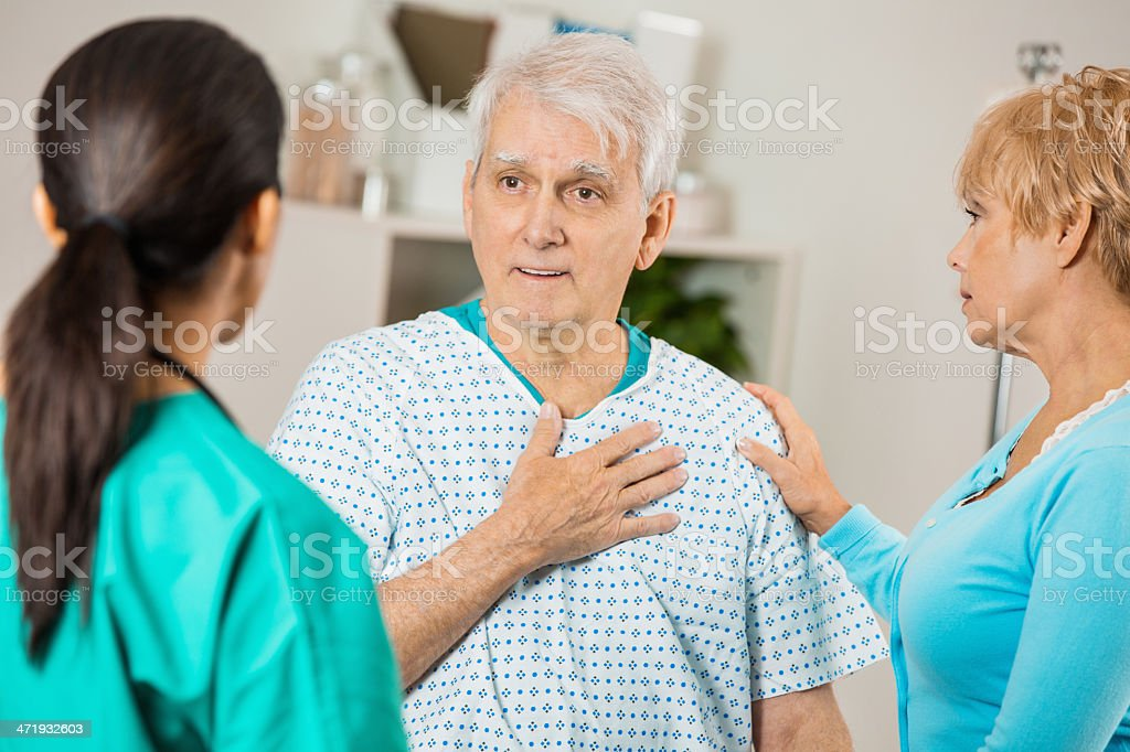 Senior patient in hospital explaining pain to doctor or nurse stock photo