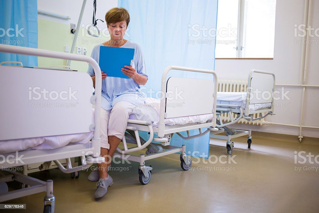 Senior patient sitting on a bed with report stock photo