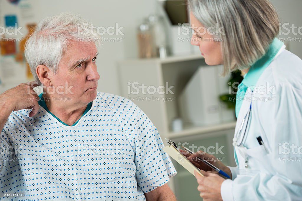 Senior patient talks with doctor about symptoms stock photo