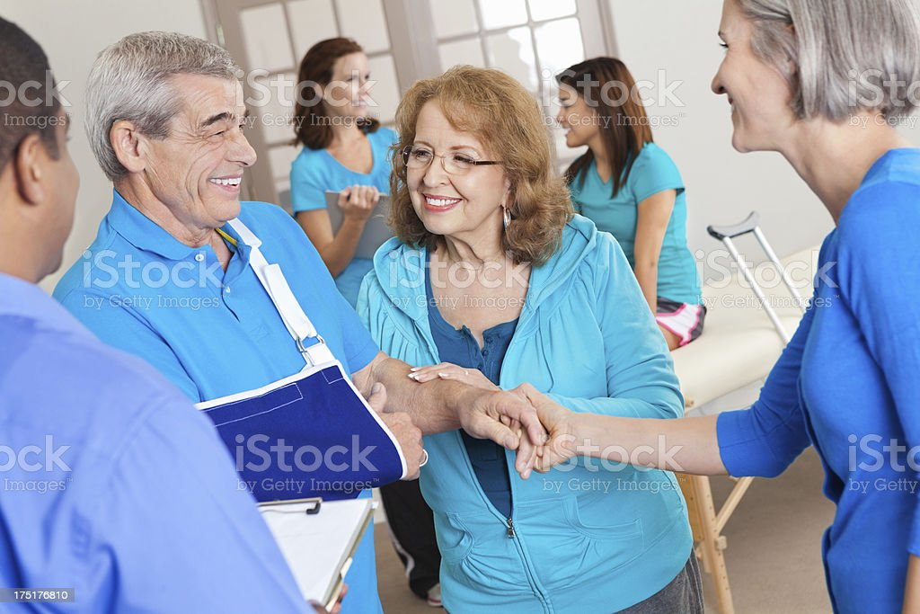 Senior patient thanking physical therapist in busy rehabilitation hospital royalty-free stock photo