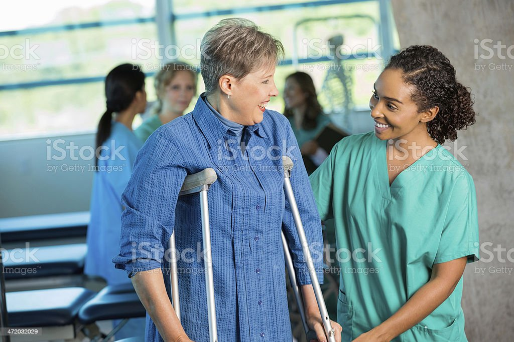 Senior patient using crutches in physical theraphy office stock photo