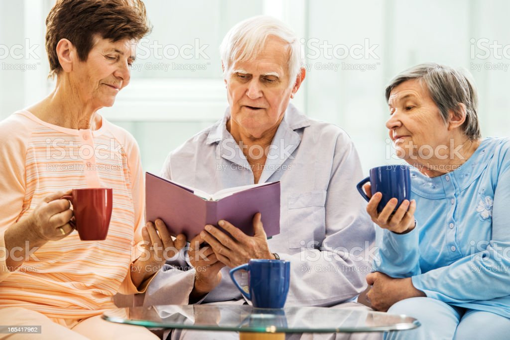 Senior people enjoying while reading a book. royalty-free stock photo