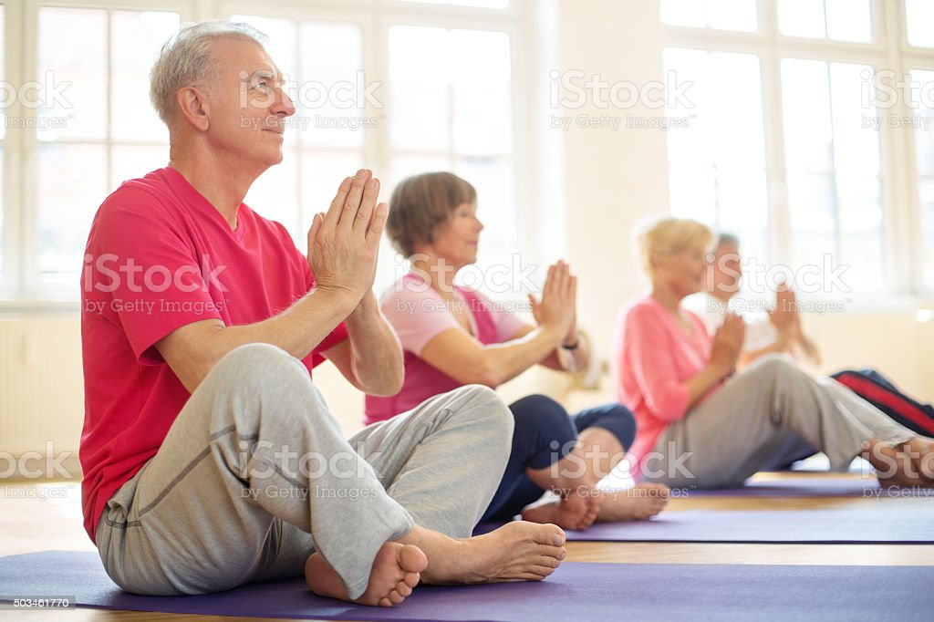 Senior man sitting in lotus position doing meditation with group of...