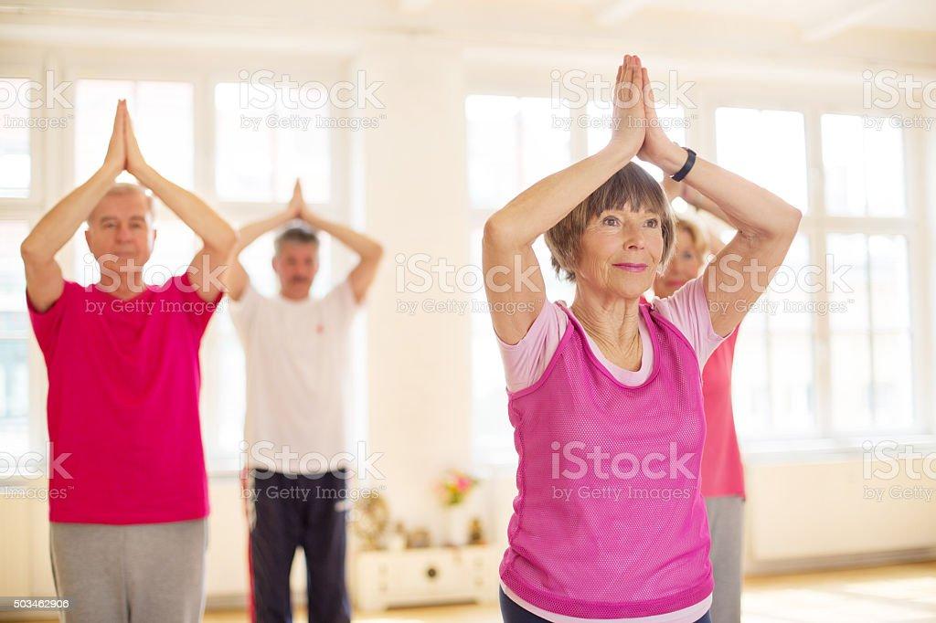 Senior people practicing tree pose yoga stock photo