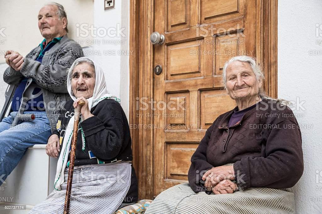 Senior people sitting in front of their house stock photo