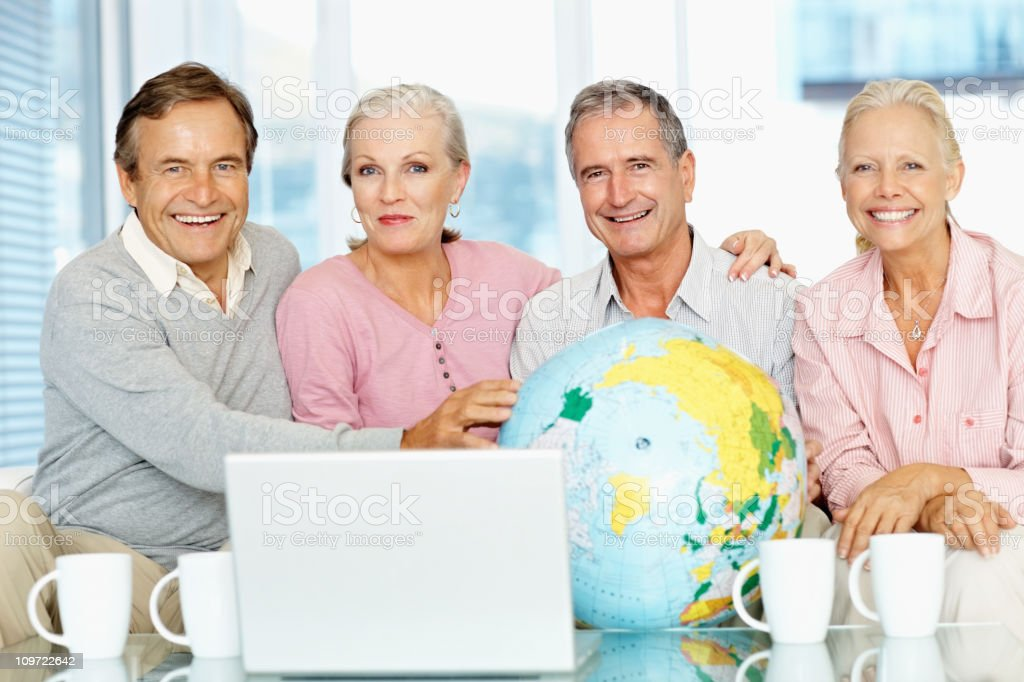 Senior people sitting over coffee with globe royalty-free stock photo
