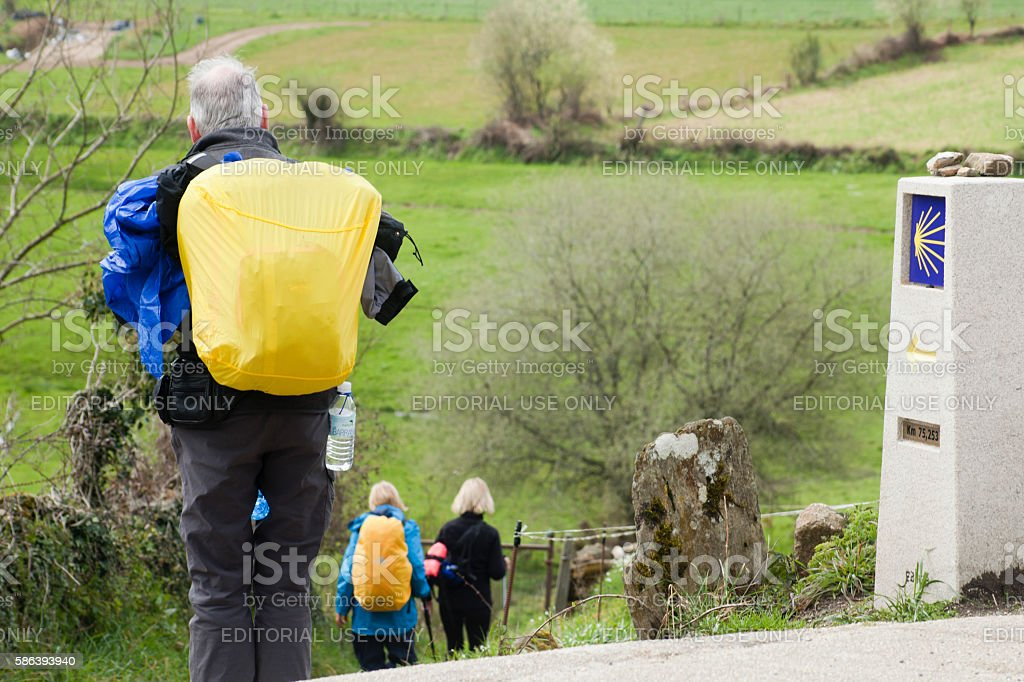 Senior pilgrims in the 'camino de Santiago', milestone. stock photo