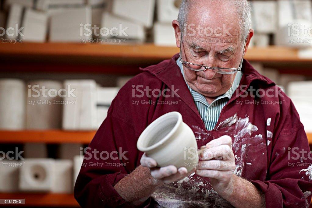 Senior potter working on a clay vase stock photo