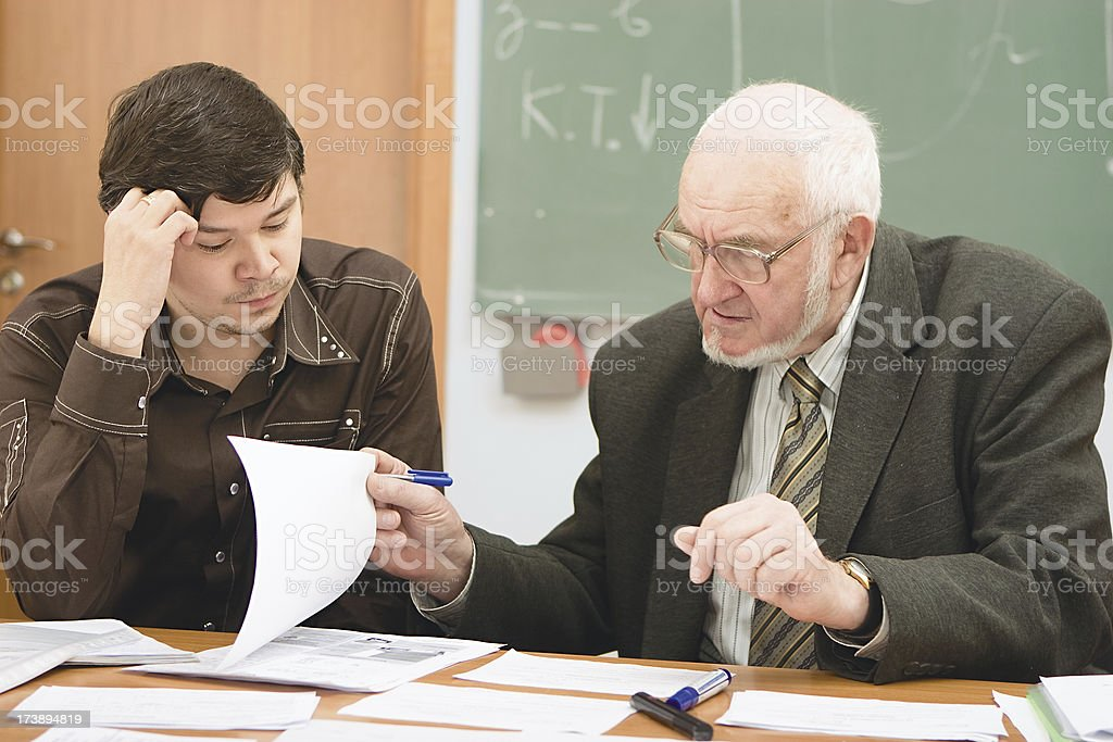 Senior professor examining the student's project royalty-free stock photo