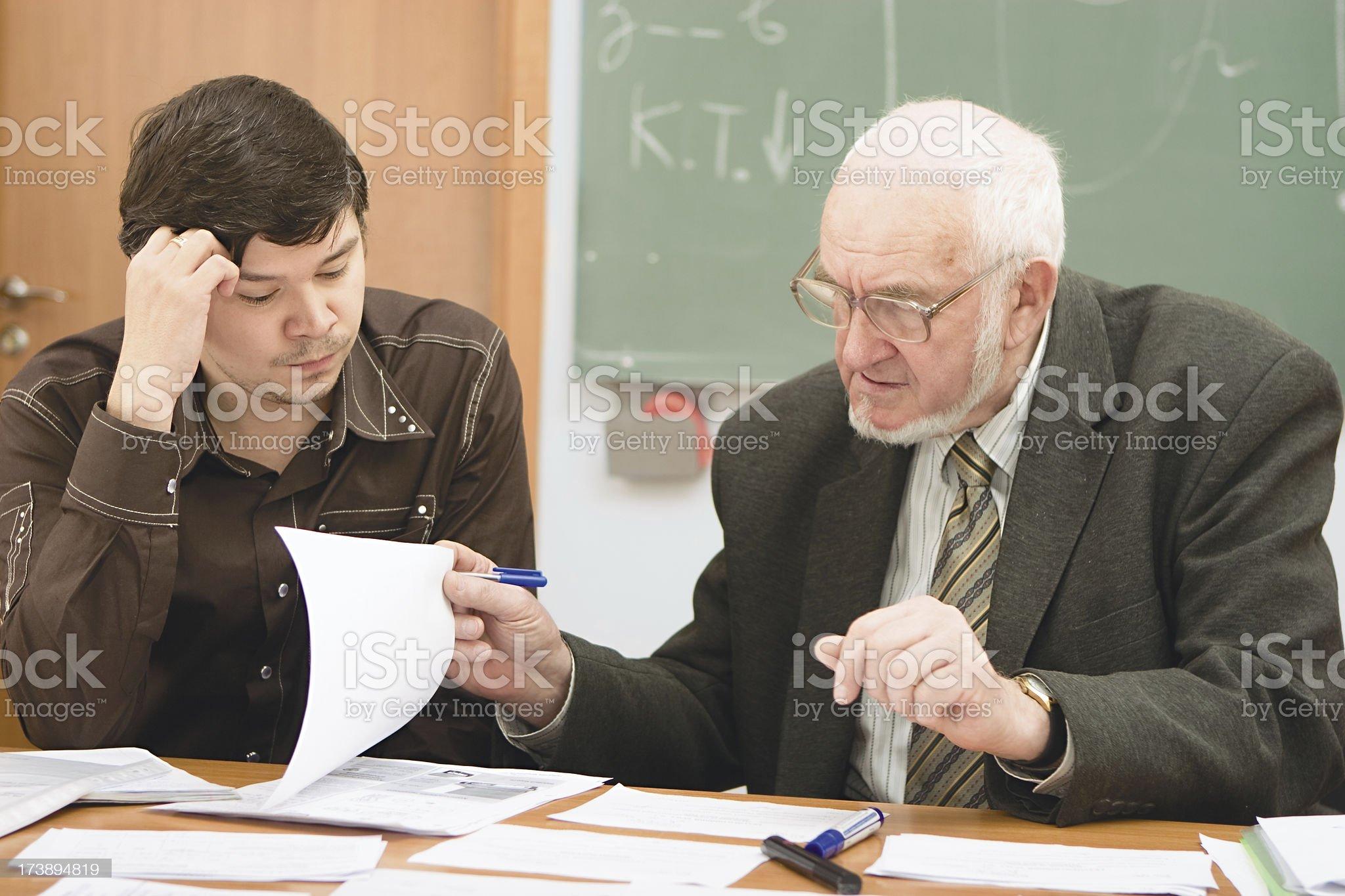 Senior professor examining the student's project royalty-free stock photo