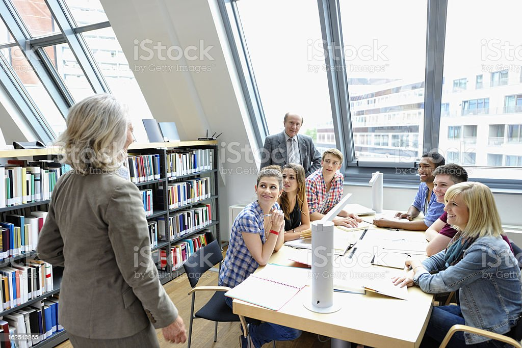 Senior Professors Holding Lecture in Library royalty-free stock photo