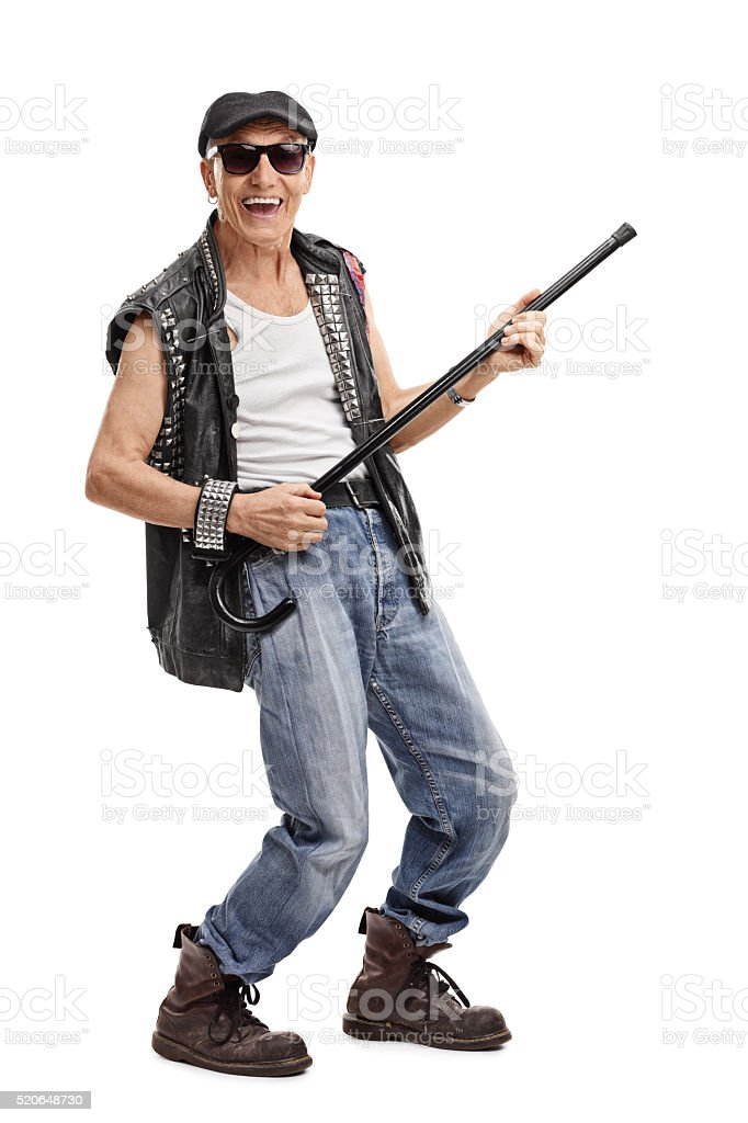 Senior punk rocker playing with a cane stock photo