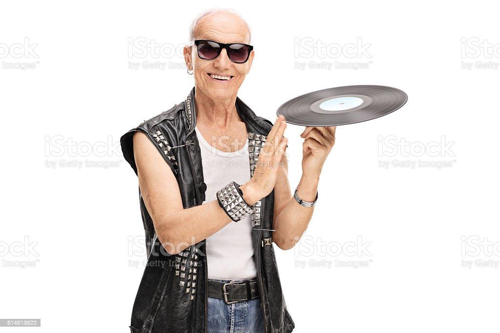Senior punk rocker spinning a vinyl stock photo