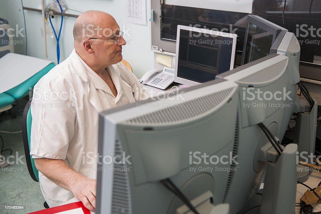 Senior radiologist of Oncology institute is examing MRI scans royalty-free stock photo