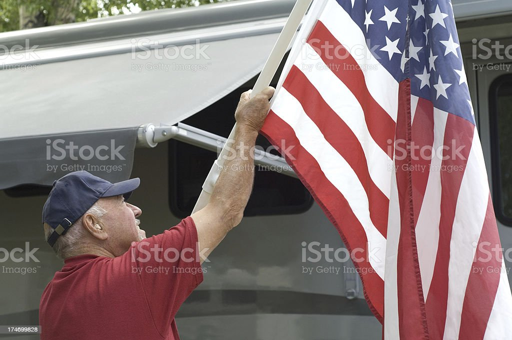 Senior Raising Flag At RV Campground royalty-free stock photo