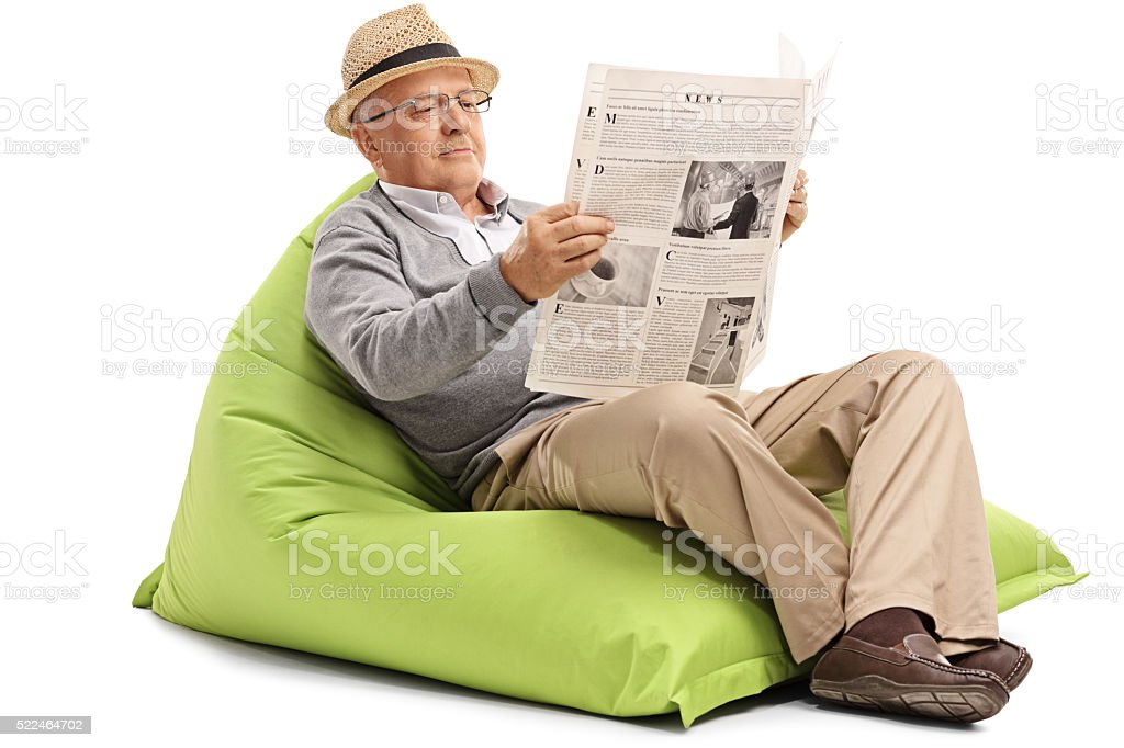 Senior reading newspaper seated on beanbag stock photo
