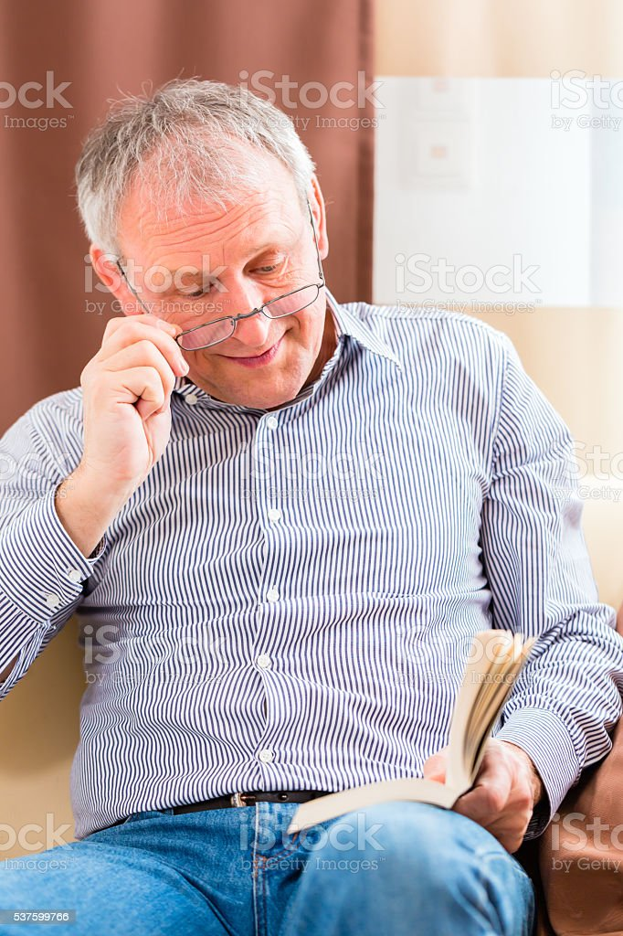 Senior reading with presbyopia book stock photo