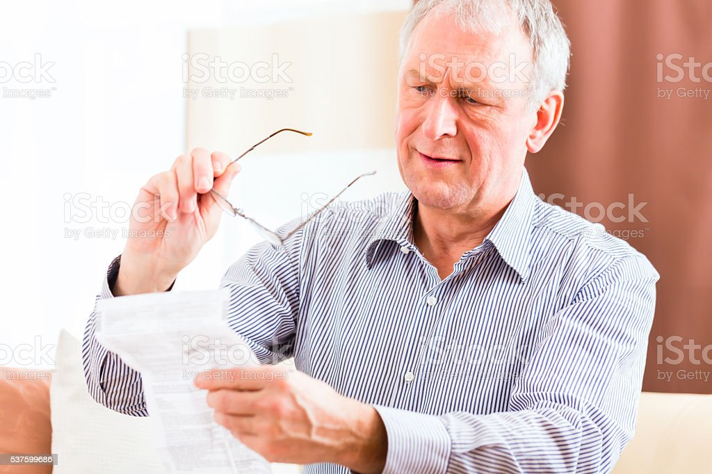 Senior reading with presbyopia package insert stock photo