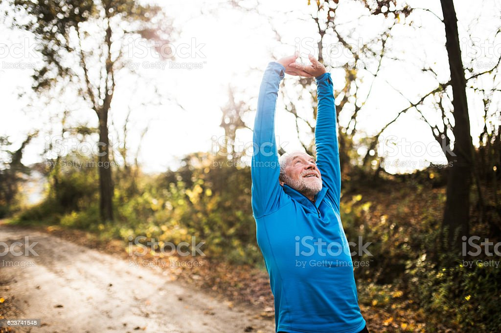 Senior runner doing stretching in sunny autumn nature. stock photo