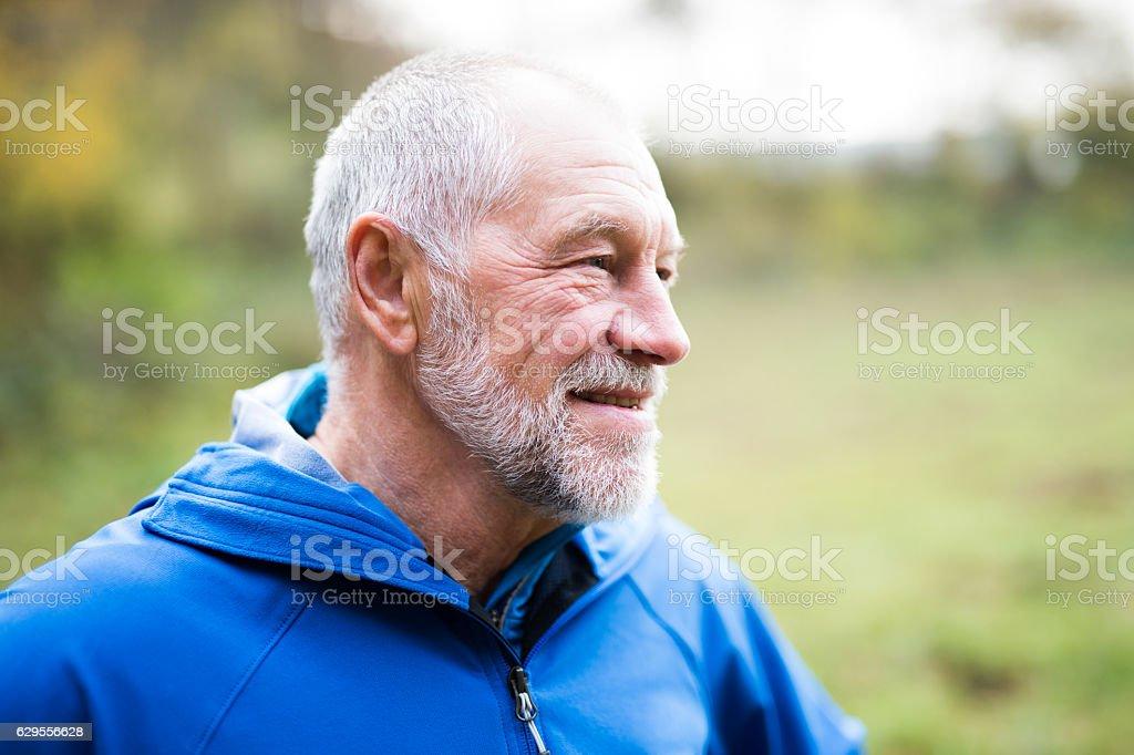Senior runner in nature. Man resting, smiling. Close up. stock photo