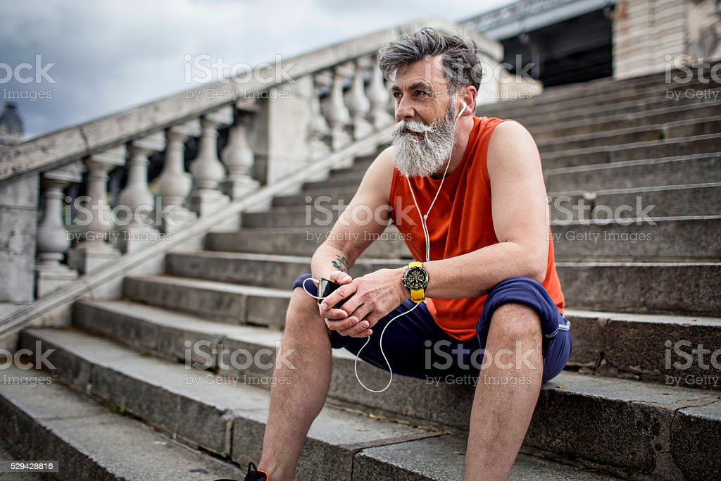 Senior runner resting on steps stock photo