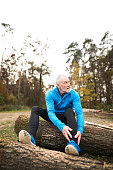 Senior runner sitting on wooden logs, man resting, stretching.