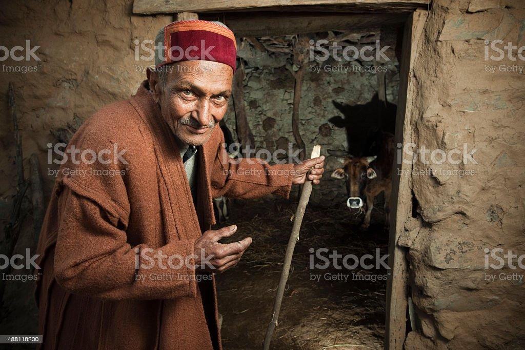 Senior rural man of Himachal Pradesh near barn. stock photo