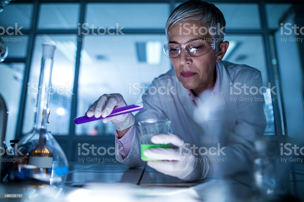 Senior scientist mixing chemical substances during her scientific experiment. stock photo
