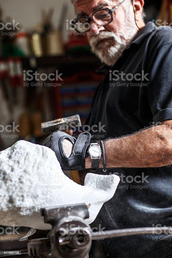Senior sculptor working on his sculpture stock photo