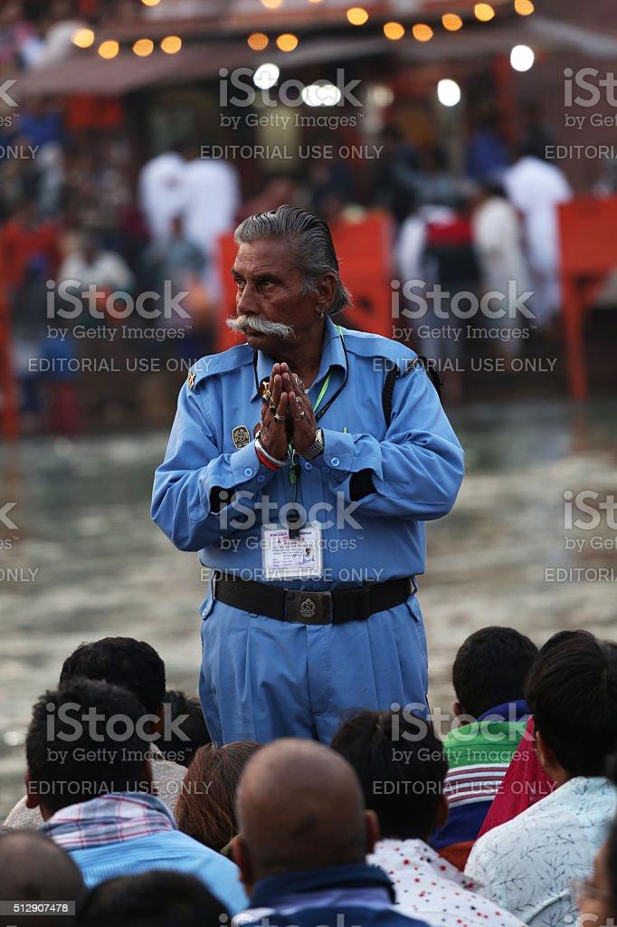 Senior security guard praying during Ganga aarti at Haridwar stock photo
