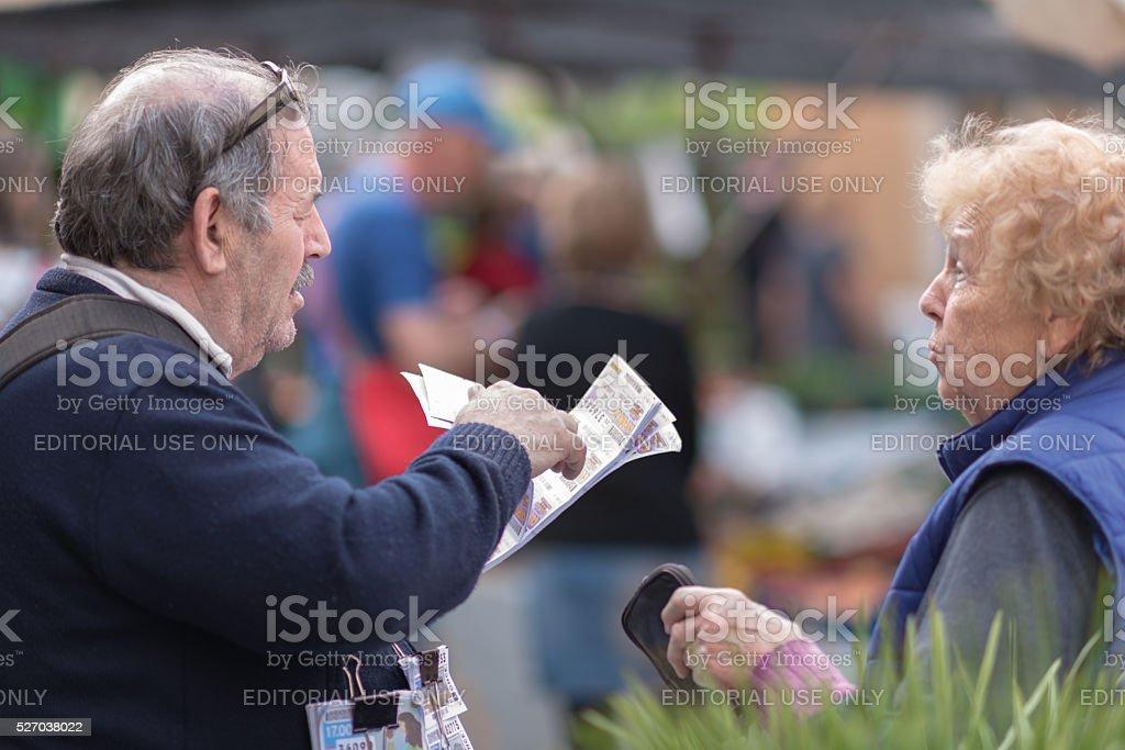 Senior selling lottery ticket at city market in Sineu Mallorca stock photo
