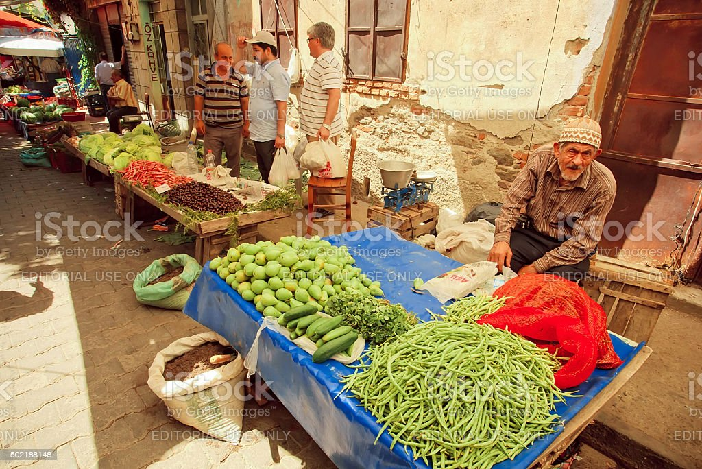Senior sells herbs, beans and pears on street market stock photo