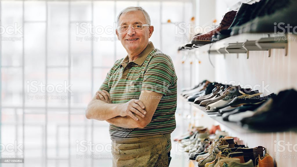 Senior Shoemaker Standing In His Shop. stock photo