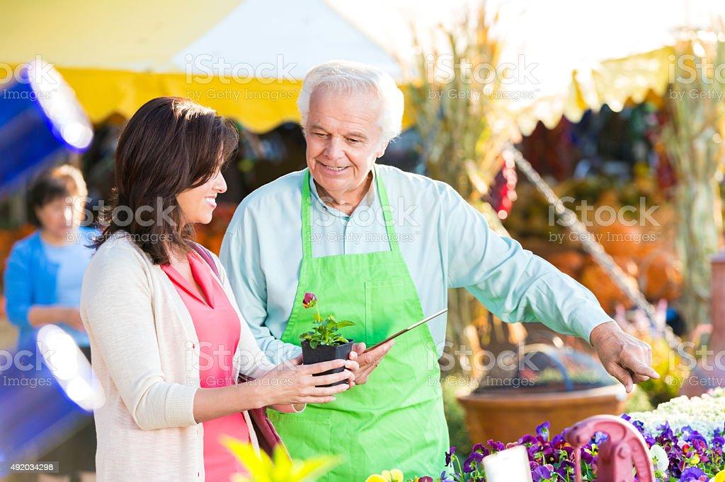 Senior shop owner helping customer in gardening store stock photo
