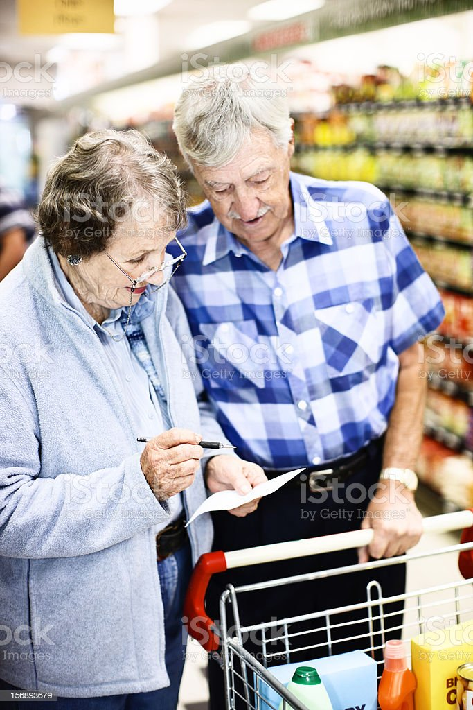 Senior shoppers check grocery list in supermarket stock photo