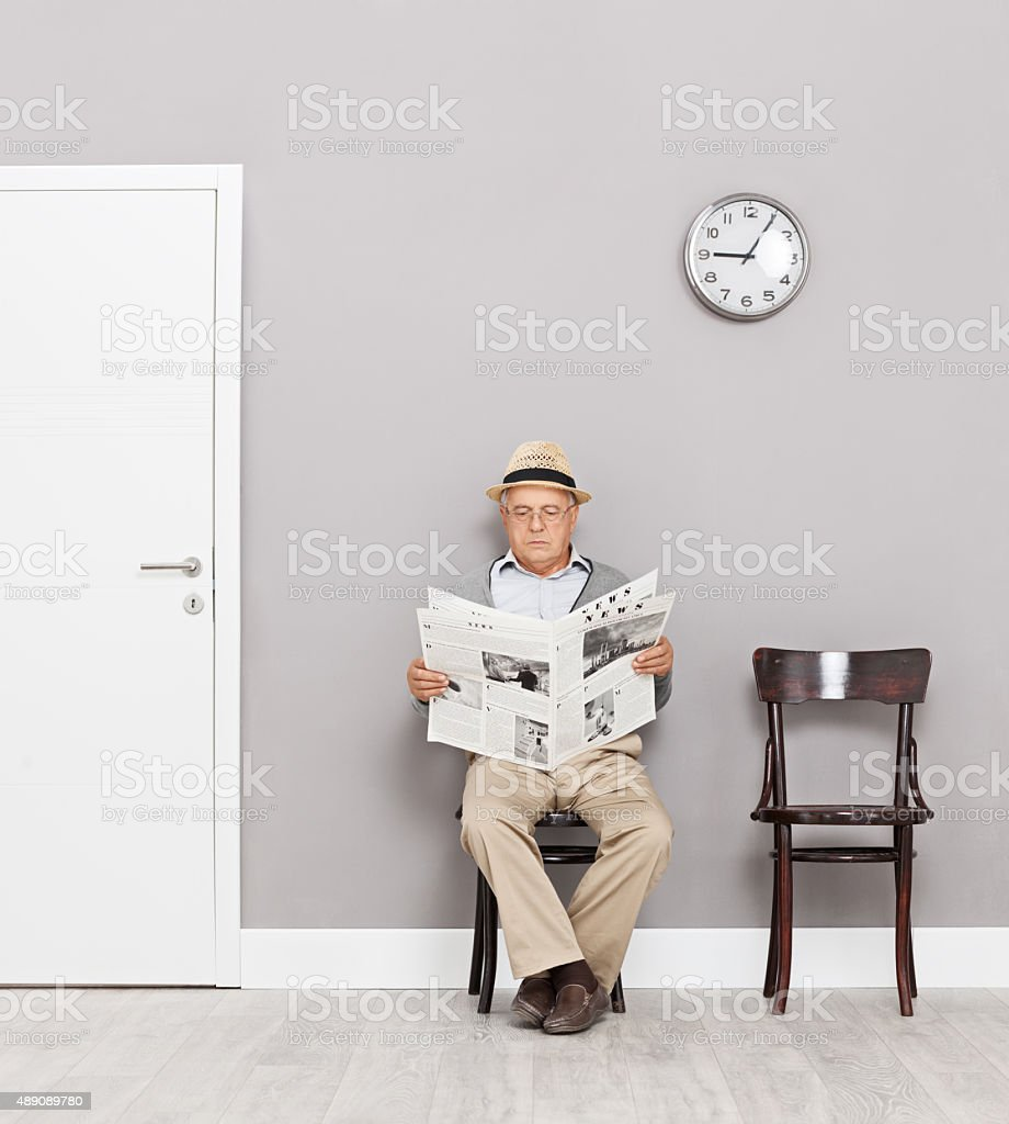 Senior sitting in a lobby and reading newspaper stock photo