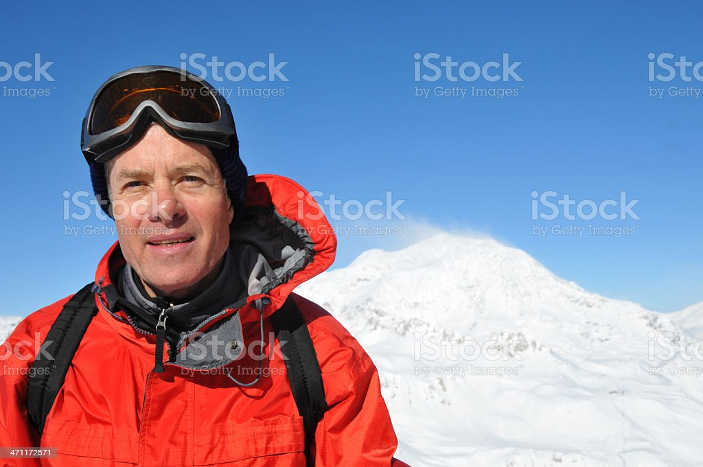Senior skier laughing in the sun against mountain royalty-free stock photo