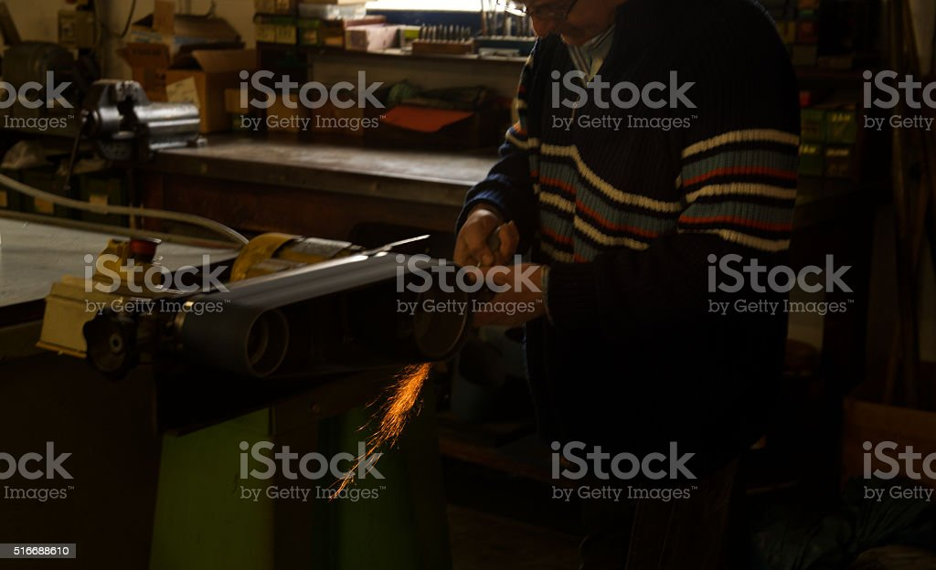 senior skilled worker in detail sanding metal with machinery stock photo