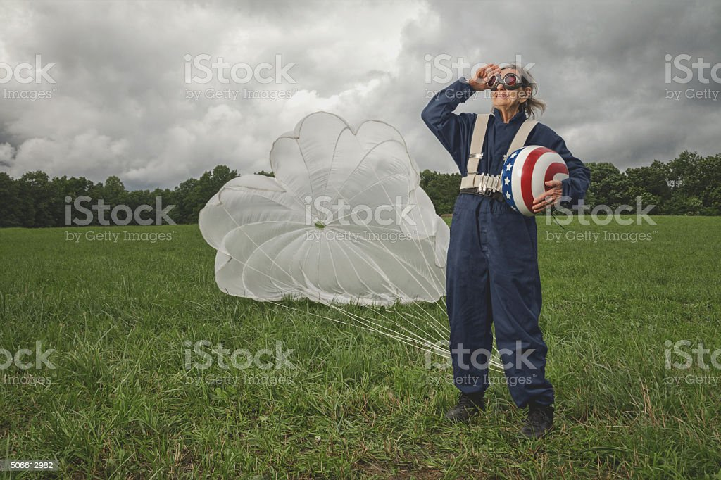 senior skydiver with helmet and parachute salute stock photo