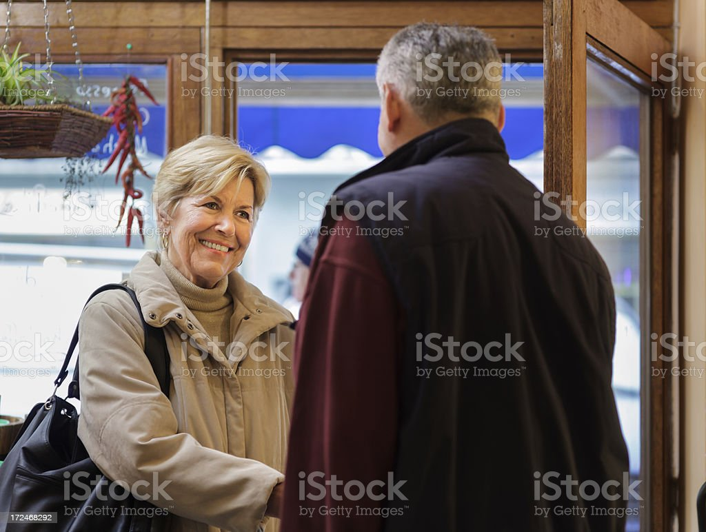 Senior small business Owner greeting a customer stock photo