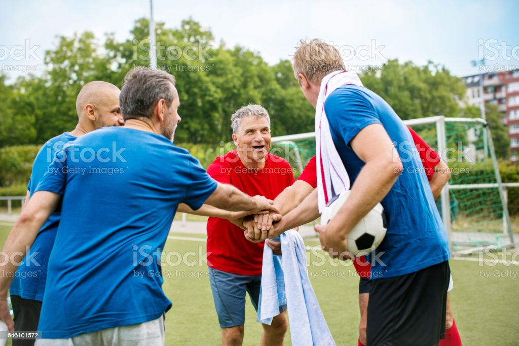 Senior soccer players putting their hands together stock photo