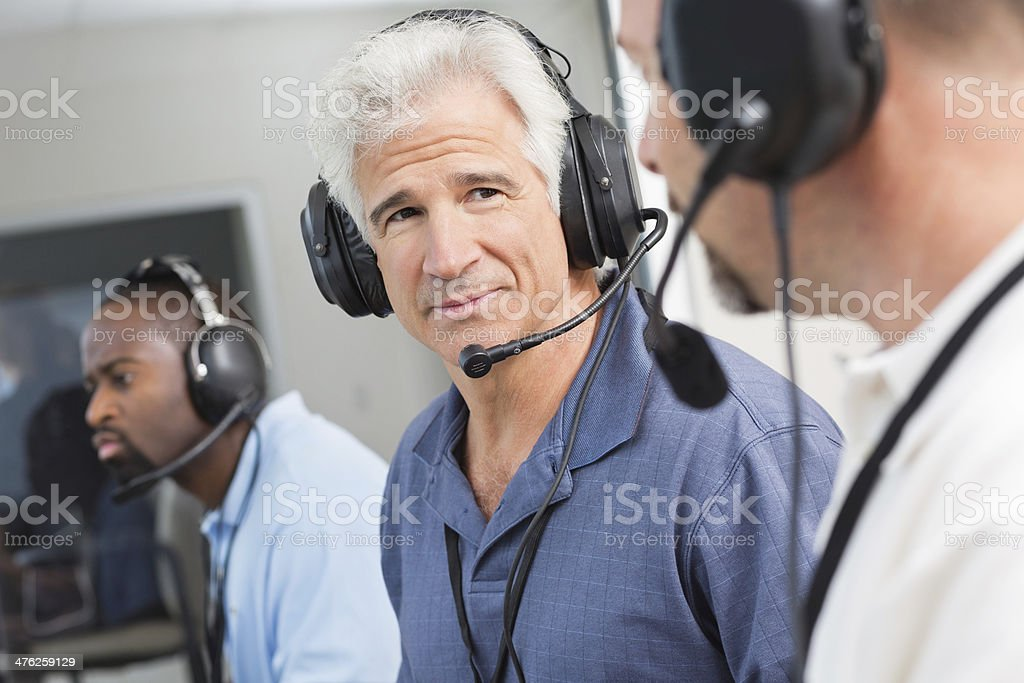 Senior sports broadcaster discussing game with colleague in press box stock photo