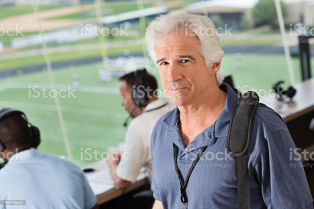 Senior sports commentator in stadium press box for football game stock photo