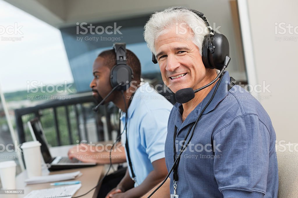 Senior sports commentator with other reporters in stadium press box stock photo