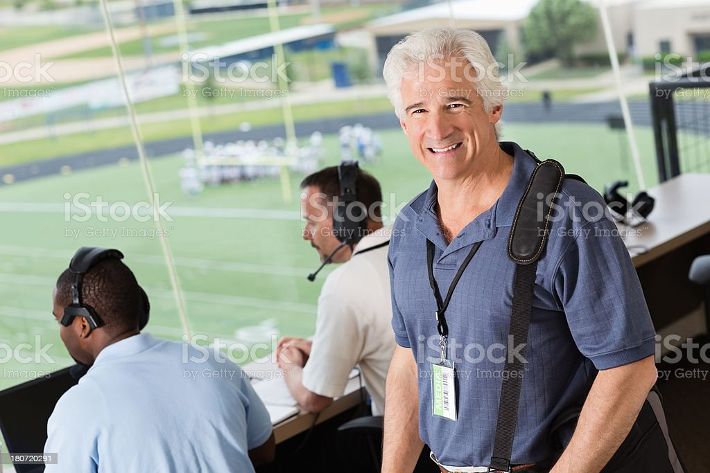 Senior sports reporter in stadium press box during football game stock photo